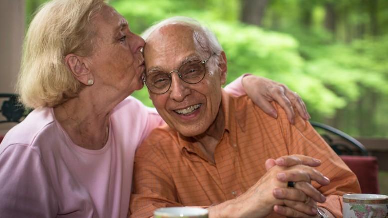 Senior woman kissing man,  smiling